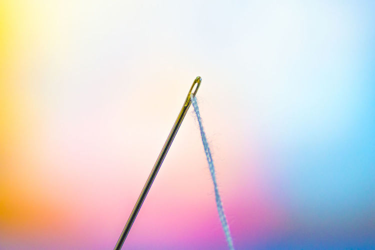 Close-Up Of Needle And Thread Against Colorful Background