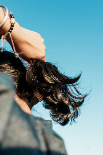 Rear view of woman adjusting hair against clear blue sky
