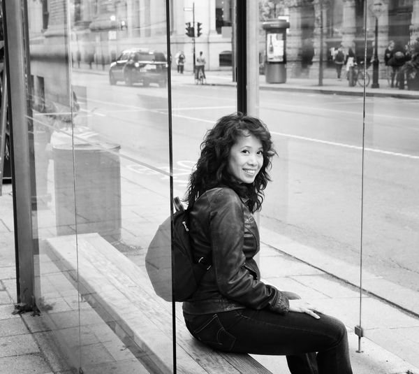 Portrait of woman sitting on glass window