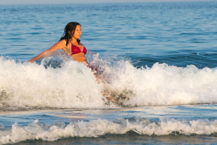 Woman in sea waves splashing on shore