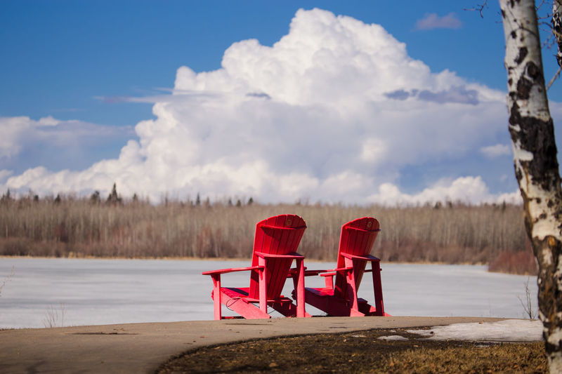 Red chair by lake against sky