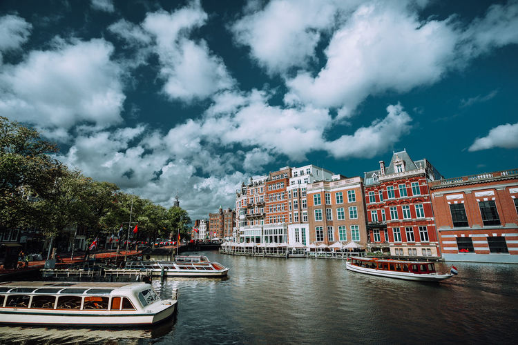 Boats on canal by buildings against cloudy sky in city