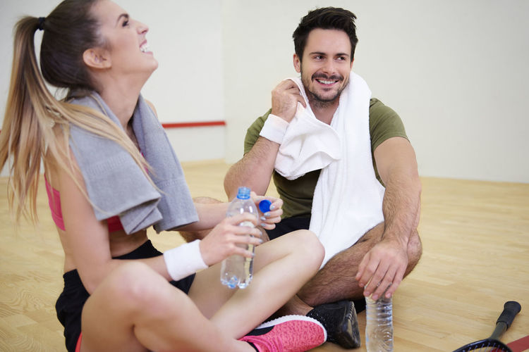 After Game Couple Laughing Sitting Tennis Bottle Of Water Break Sport Squash Tennis Court Timebreak Women