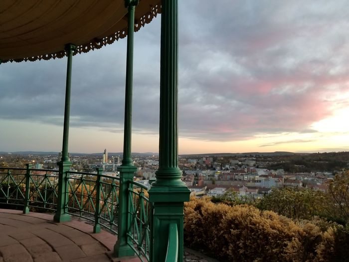 A sunset view from the gazebo. Europe Czech It Out Hand Rail Wrought Iron Bushes Plant Life Horizon Overlook Gazebo Pillars Architecture Skyline Park - Man Made Space Europe Sky Cloud - Sky Cityscape Sunset Urban Skyline Panoramic City Urban Sprawl Roof Rooftop Tiled Roof