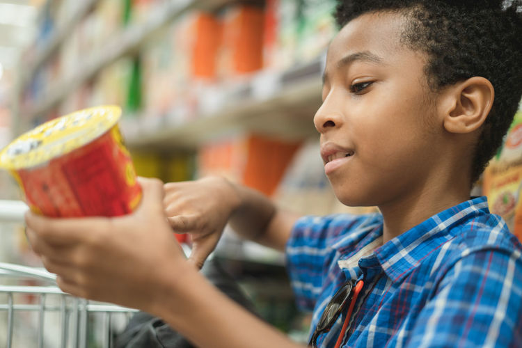Cute African American kid reading the chips label on a supermarket mall Human Limb Child One Person Childhood Boys Men Headshot Looking Selective Focus Food And Drink Close-up Lifestyles Indoors  Real People Portrait Males  Profile View Side View Holding Reading Packaging African Afro American Afro-american African-american African American Kid Cute 8 Years Old Curly Hair Chipster Chips Packgage Supermarket Mall Cart Store Blackandwhite Latin Descent Descending