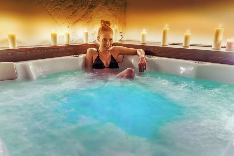 Happy Woman Sitting In Jacuzzi By Illuminated Candles