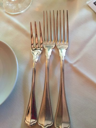Three forks on linen tablecloth -