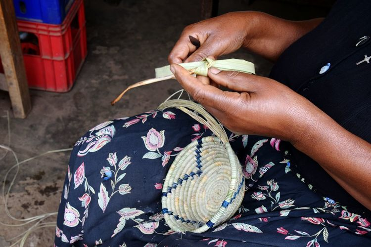 Midsection of woman making basket