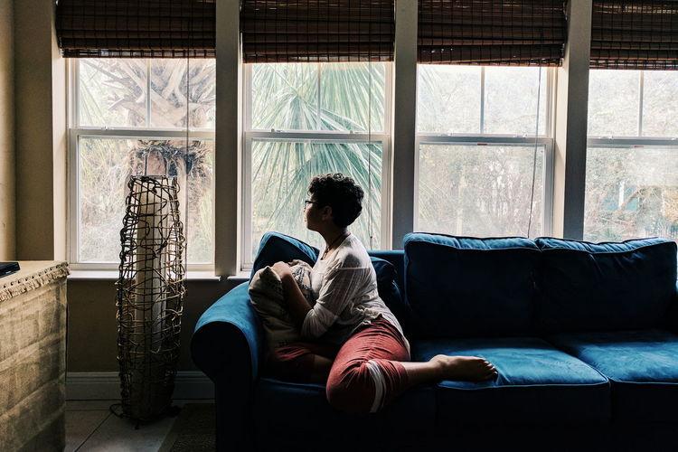 Teenage girl sitting on sofa by window at home