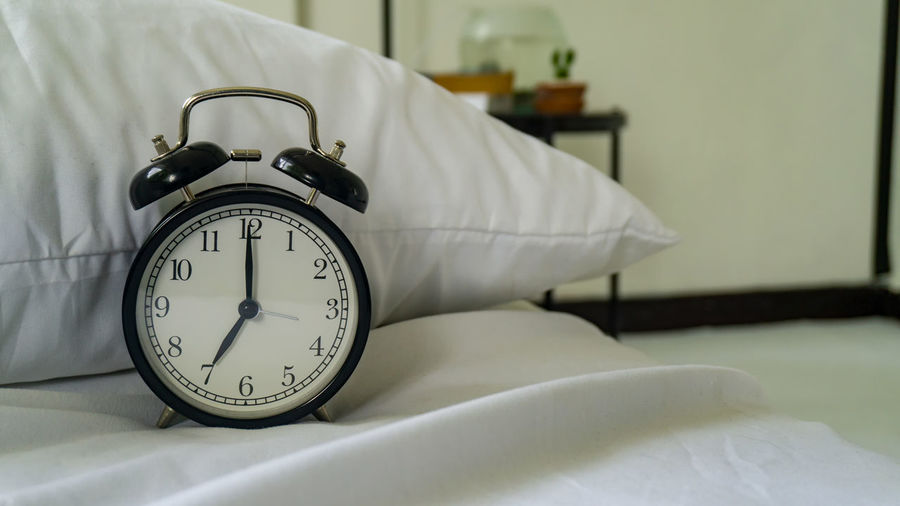 Close-up of alarm clock on bed