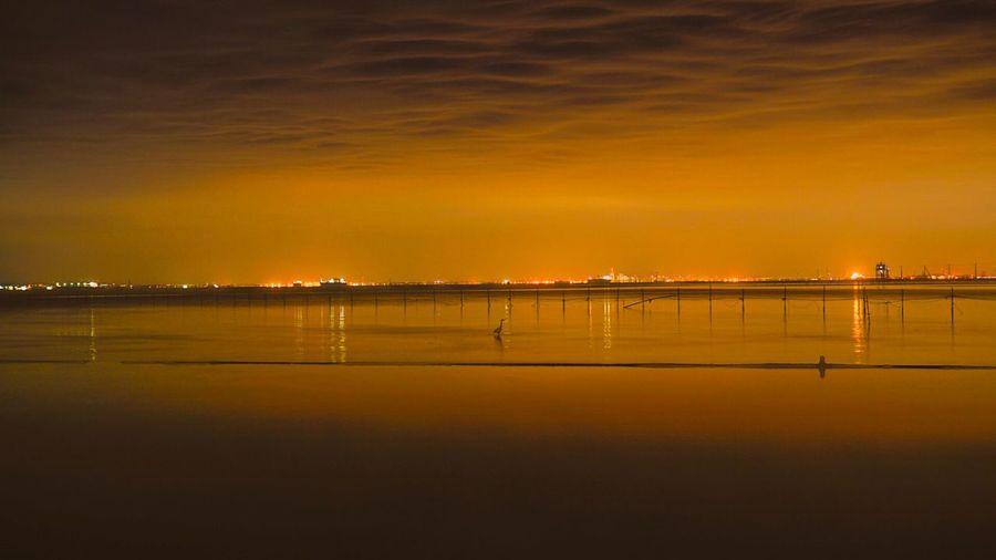 Scenic View Of Calm Lake Against Orange Sky