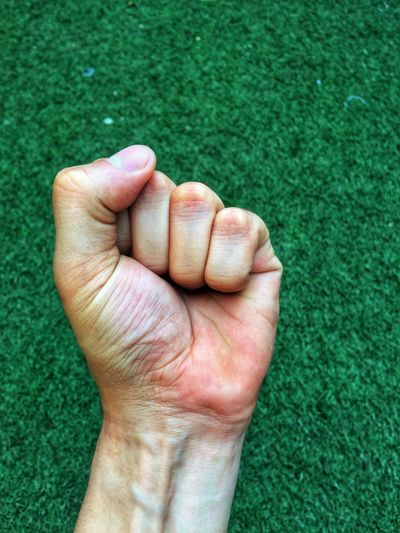 Cropped Hand Clenching Fist Above Grass