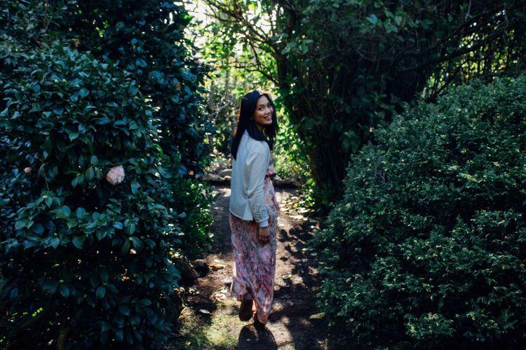 Rear view portrait of happy woman walking amidst plants at park