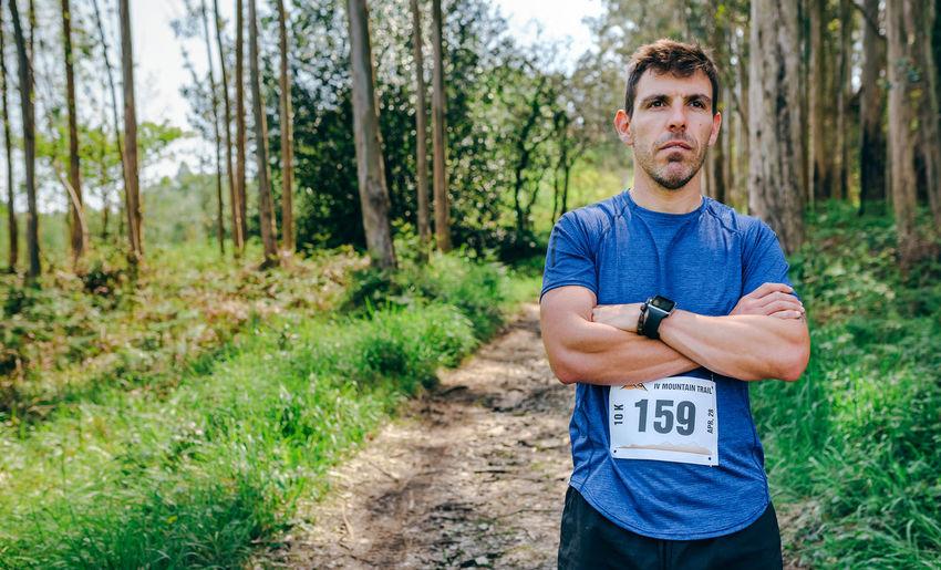 Man standing with marathon bib in forest
