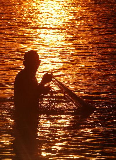 Fisherman Spreading Fishing Net In Sea