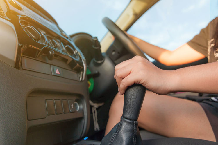 Midsection of woman driving car