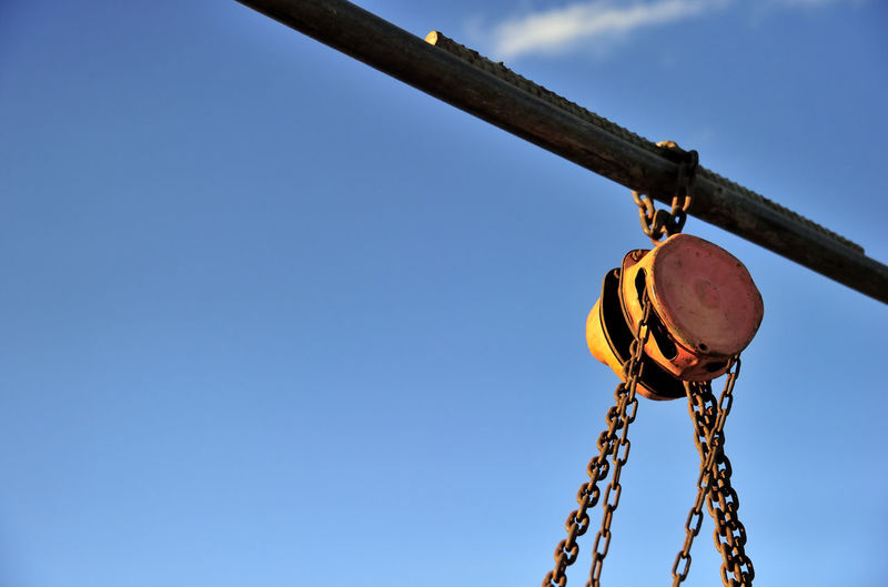 Low angle view of chain and pulley against sky on sunny day
