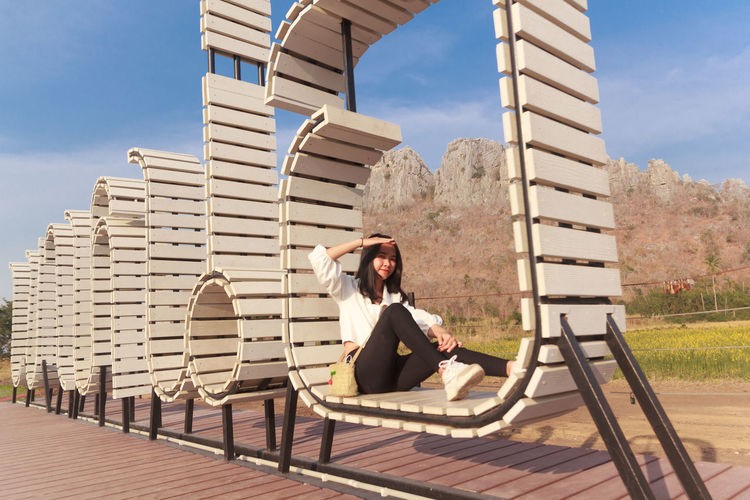 Woman sitting in front of built structure