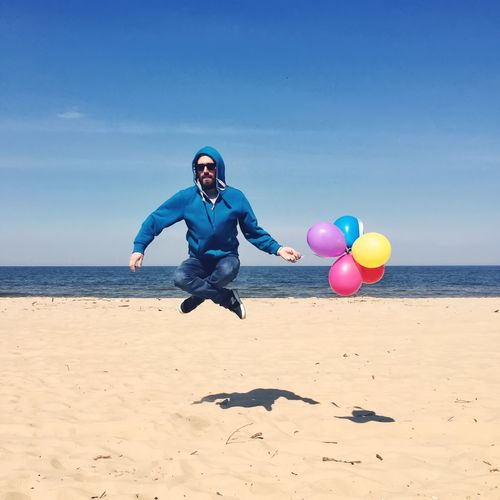 Full Length Of Man In Mid-Air With Multi Colored Balloons At Beach