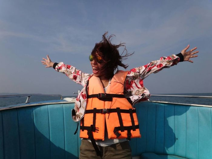Happy woman wearing life jacket standing with arms outstretched on boat deck
