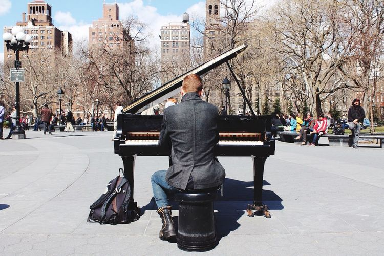Rear View Of Man Playing Piano