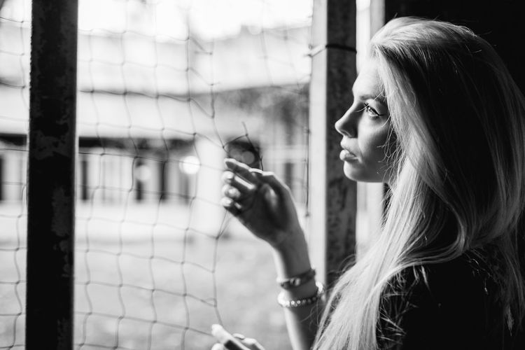 Side view of thoughtful young woman standing by window