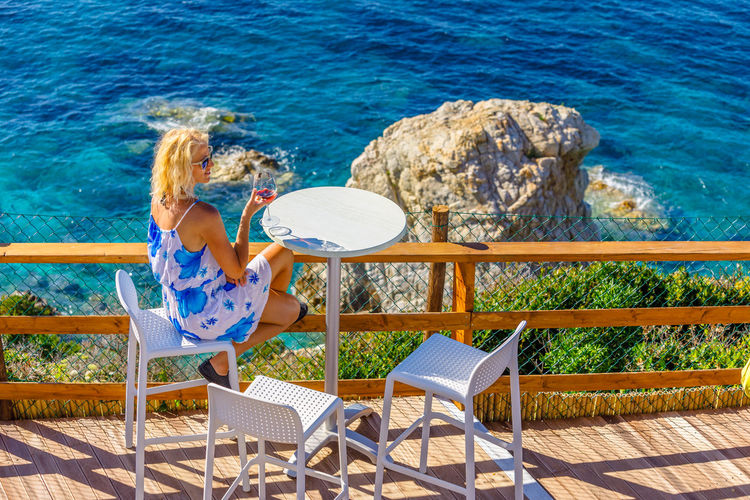 Rear view of woman sitting on chair by sea