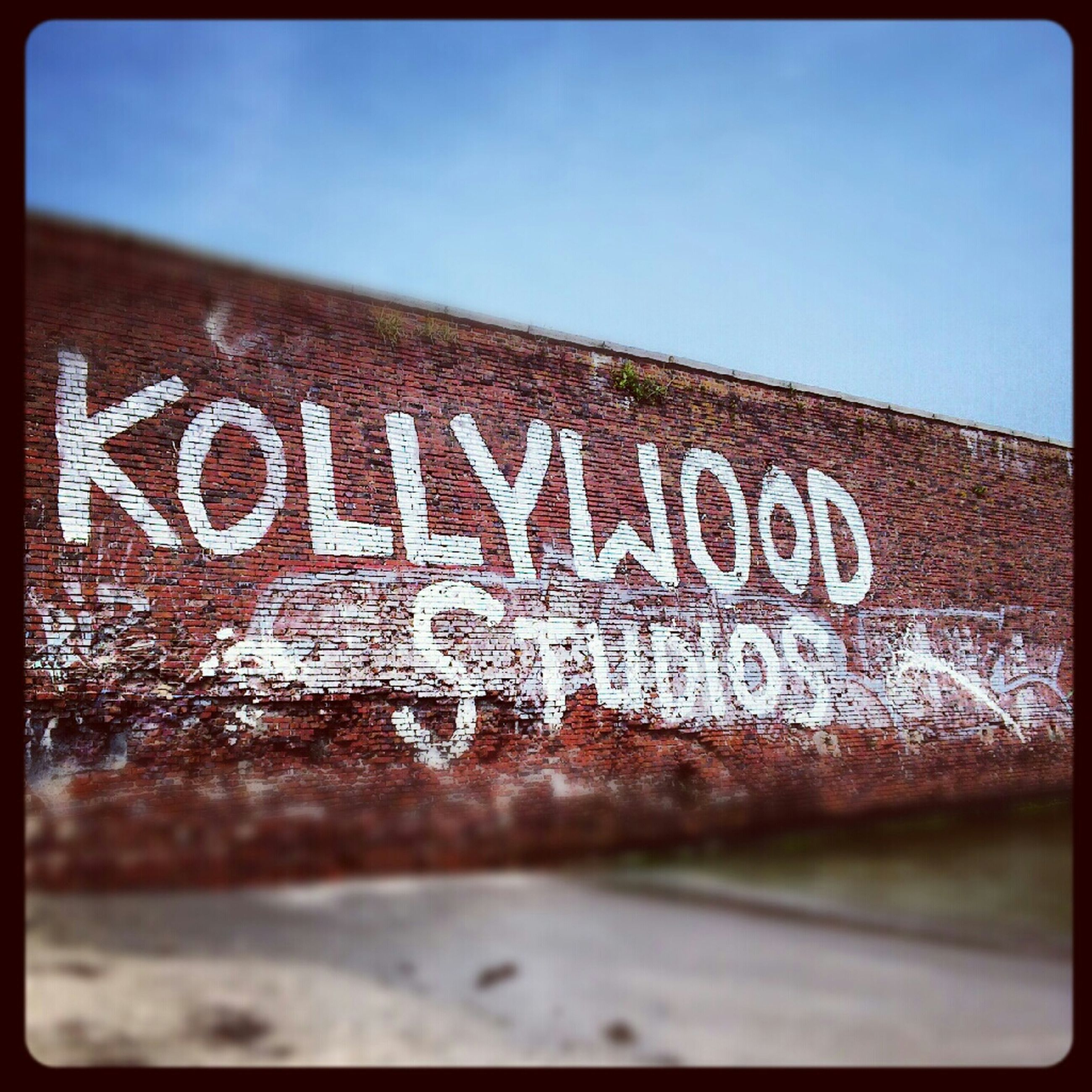 text, western script, transfer print, communication, auto post production filter, capital letter, close-up, clear sky, non-western script, built structure, graffiti, wall - building feature, damaged, architecture, wall, information, old, weathered, day, no people