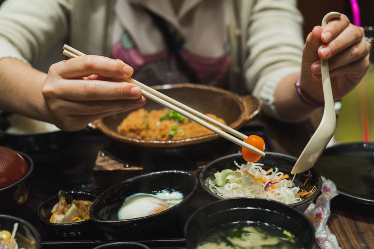 Close-up midsection of woman having meal with chopsticks at table