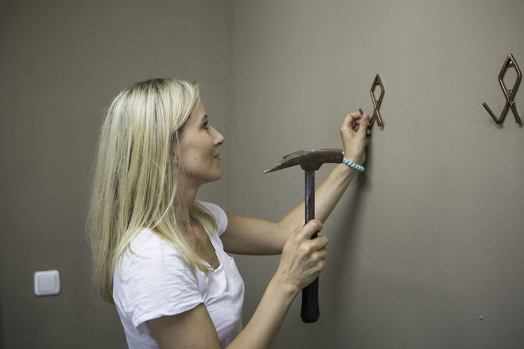 Side view of woman hammering coat hook on brown wall