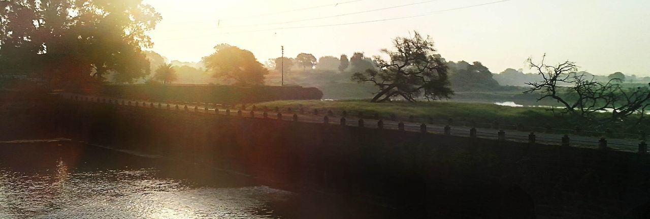 tree, water, nature, river, beauty in nature, scenics, tranquility, tranquil scene, outdoors, no people, mist, sunlight, day, clear sky, landscape, growth, sky, architecture, building exterior