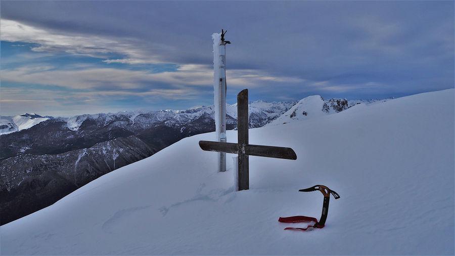 Cross on snow covered land against sky
