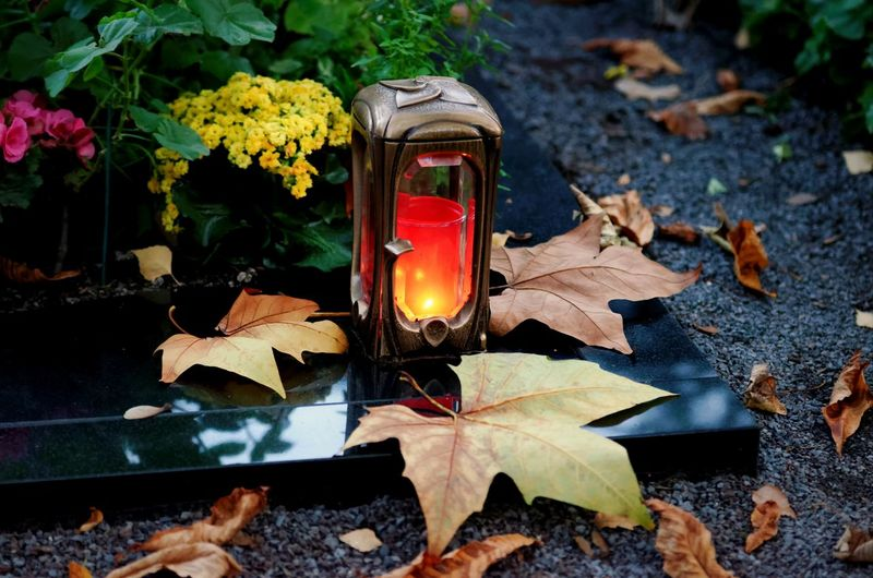 Grave light in evening mood on a cemetery with autumn leaves