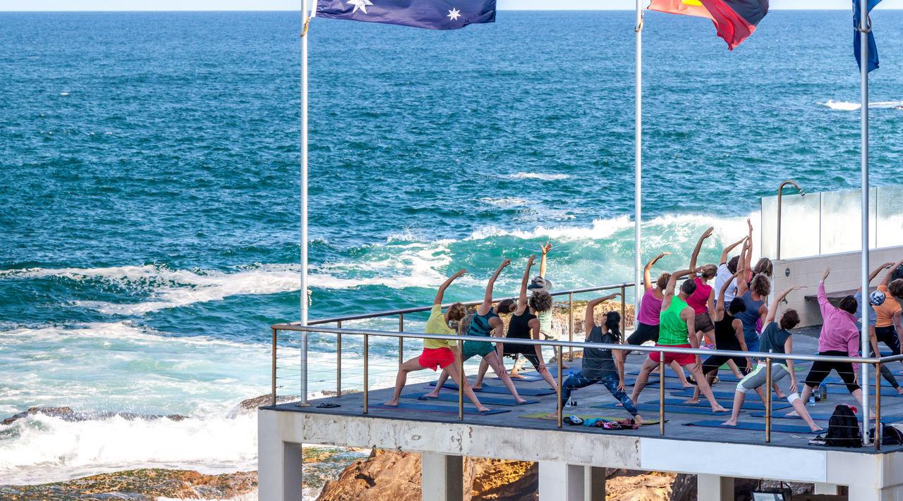 People practicing aerobics on pier against sea
