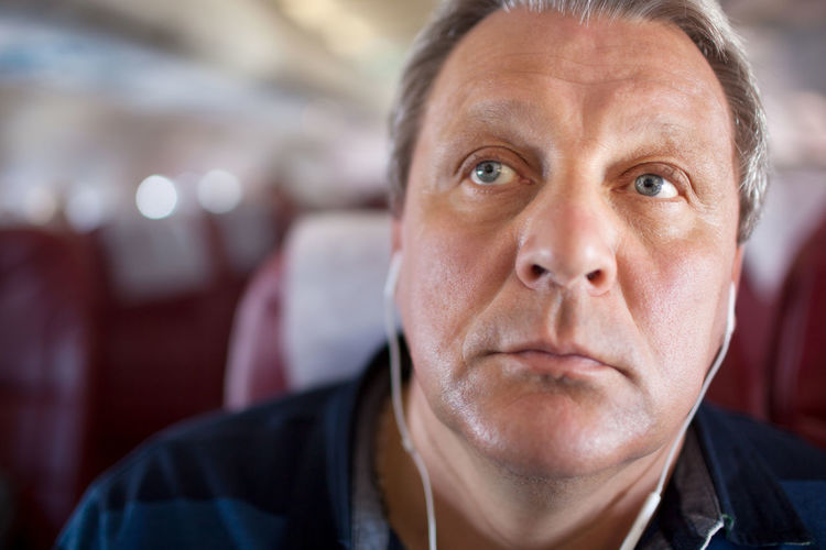 Close-Up Of Man Listening Music From Headphones In Airplane
