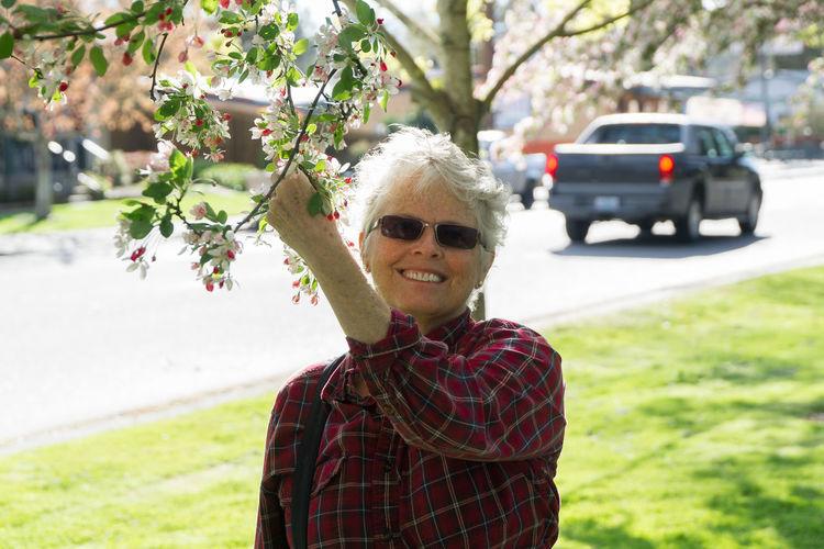 Portrait of smiling senior woman holding branch