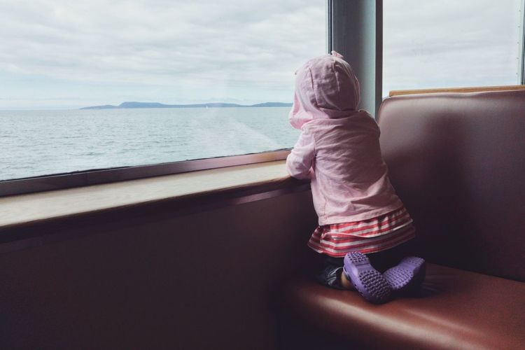 Rear view of girl looking through ferry window while wearing hooded shirt
