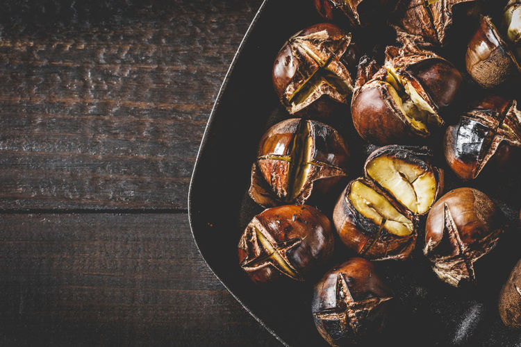 Roasted edible chestnuts in cast iron skillet over rustic wooden table. Autumn Chestnut Chestnuts Cooking Iron Meal Snack Brown Food Fried Fruit Gourmet Healthy Heap Ingredient Nut Opened Pan Roasted Roasting Seasonal Sweet Tasty Traditional Wooden