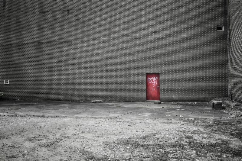 Street Photography Black And White Pop Of Color Outside Outdoors Brick Building Wall Door Red Door FAR AWAY Vacant Lot The Street Photographer - 2016 EyeEm Awards