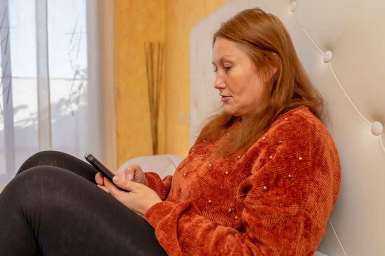 Mature woman using mobile phone while sitting on sofa at home