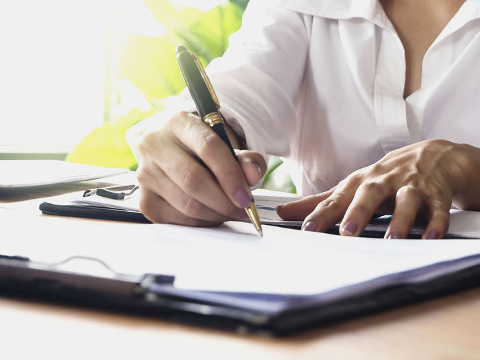 Table Pen One Person Human Hand Writing Real People Indoors  Paper Hand Midsection Holding Writing Instrument Men Occupation Selective Focus Desk Office Human Body Part Sitting Paperwork