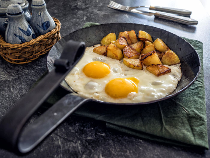 High Angle View Of Fried Egg With Potatoes In Frying Pan On Table