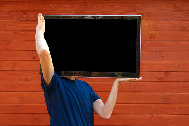 Man carrying television set while standing against wall