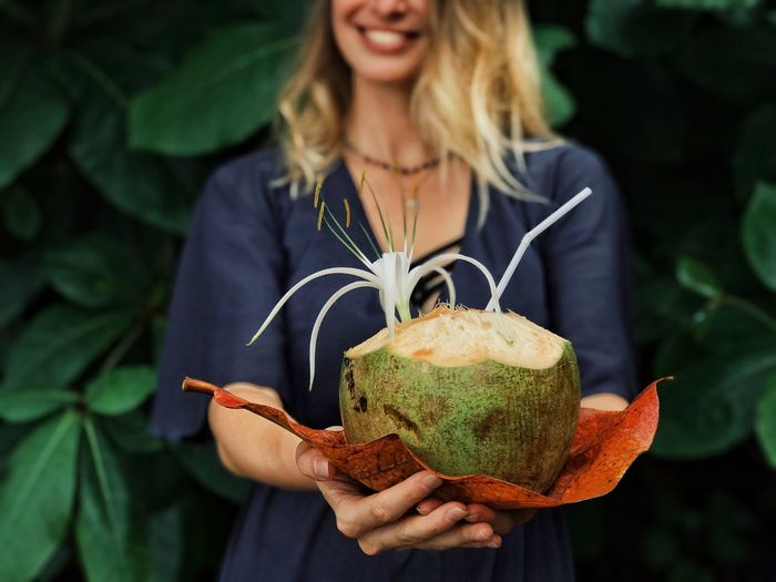 Midsection of smiling young woman holding coconut