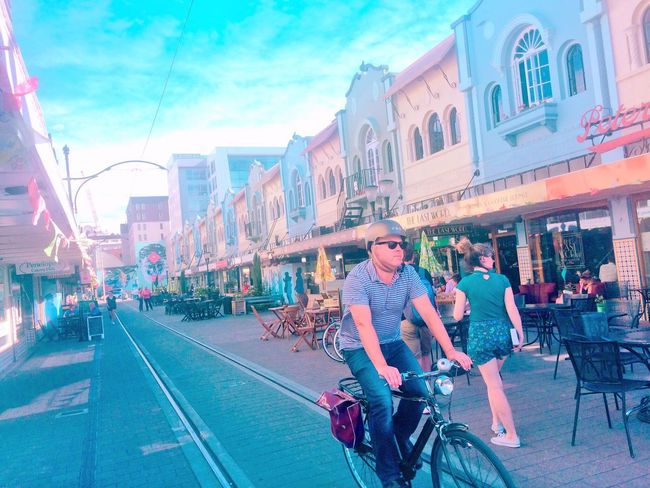 City Bicycle Multi Colored Building Exterior City Life Casual Clothing Street Built Structure Transportation Architecture City Street Outdoors Young Women Sky Mode Of Transport Young Adult Men Real People Leisure Activity Adult