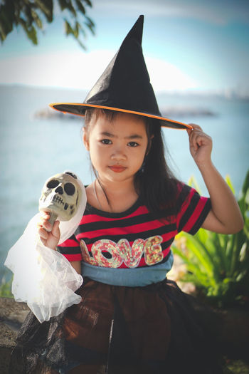 My little witch, Halloween day.. Cosplay Halloween Sunlight Asian Girl Black Hair Child Childhood Clothing Costume Day Females Focus On Foreground Front View Girl Girls Hat Holding Innocence Kid Leisure Activity Lifestyles Little Girl Looking At Camera Magic One Person Outdoors Playful Portrait Real People Skull Smilling Witch Women Wonder Young Adult