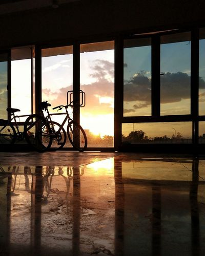 Silhouette bicycle by window against sky during sunset