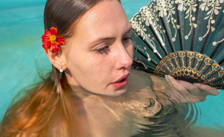 Woman holding hand fan in swimming pool