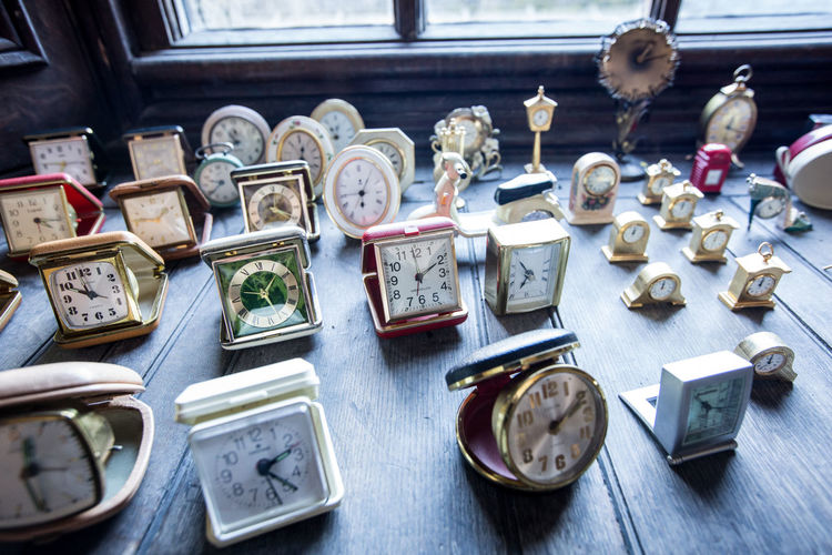 Collection of clocks on window sill Variation Choice Large Group Of Objects Antique No People Table Still Life Indoors  High Angle View Abundance Arrangement Collection For Sale Old History Day Retail  The Past Wood - Material Clock Clocks Collection Of Clocks