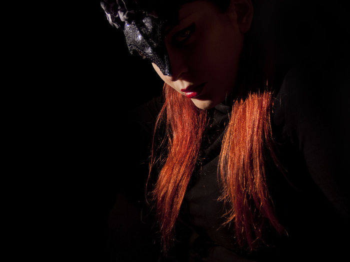 Portrait of redhead woman wearing mask against black background